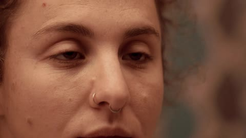 Woman With Two Nose Piercings Looking At Herself Closely In The