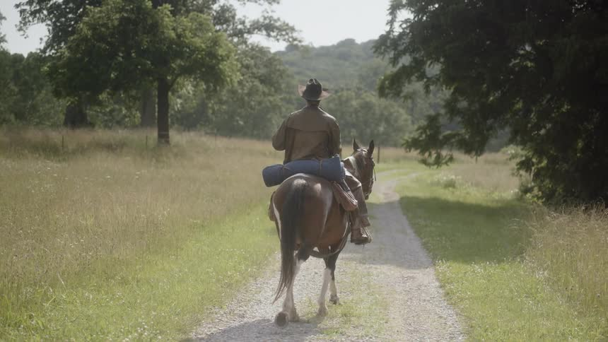 9a9d8740038 A man is riding a horse down a gravel road Stock Footage