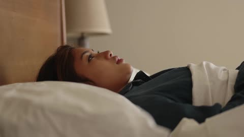 a woman is laying on a bed thinking stock footage filmsupply