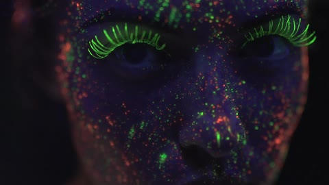 Woman With Neon Glow In The Dark Paint Stares In A Dark Room Stock