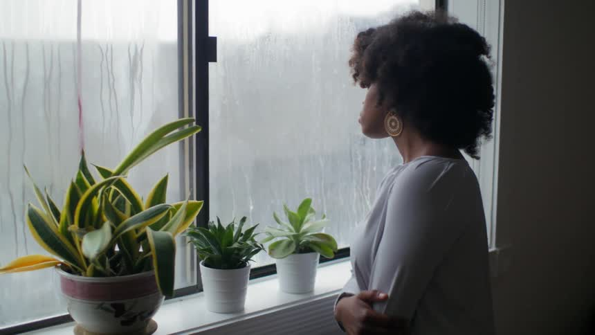 Woman Walks To Her Window To Look At The Rain Outside Stock Footage